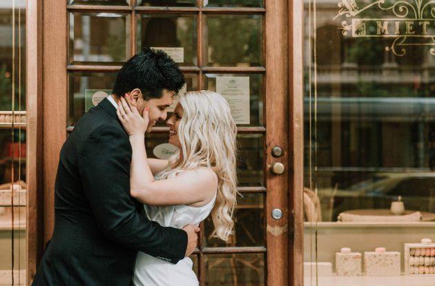 romantic couple portrait outside cute macaron store La Belle Miette