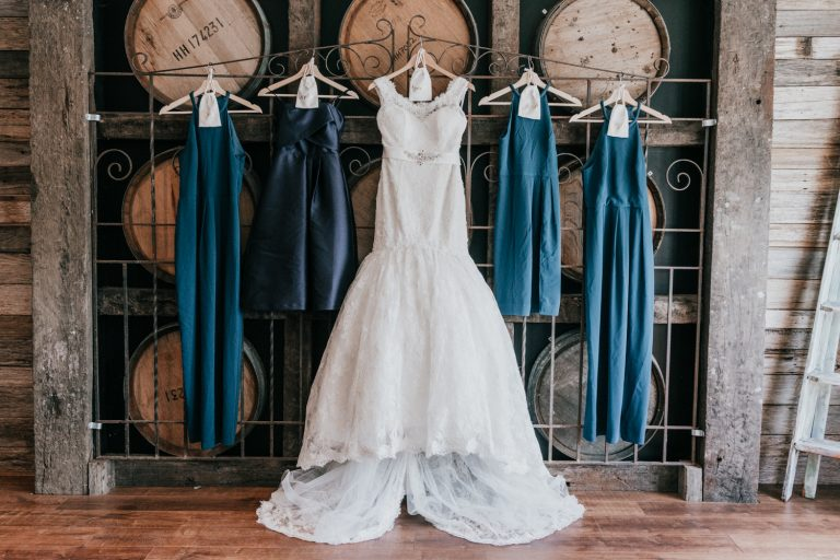 bridal wedding gown and bridesmaid dress hanging on rustic barn wedding venue