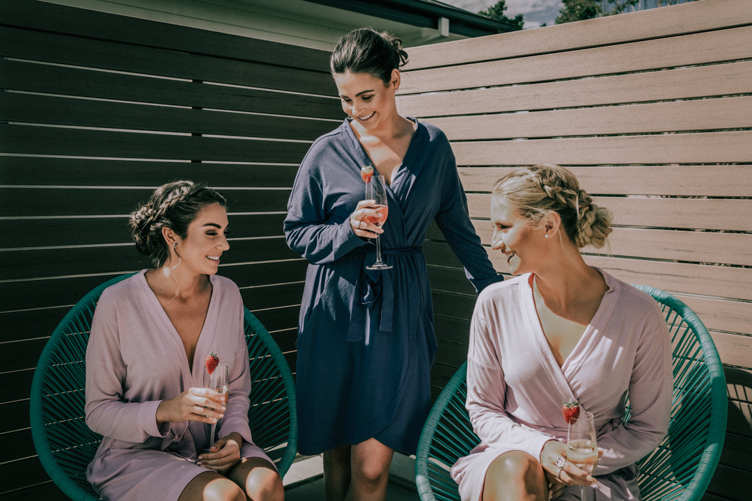 bride and bridesmaids chill out with champagne candid moment by Black Avenue Productions