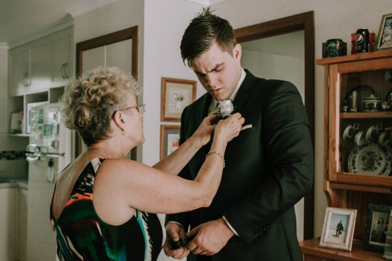 mother of groom helping son to fix up wedding suit