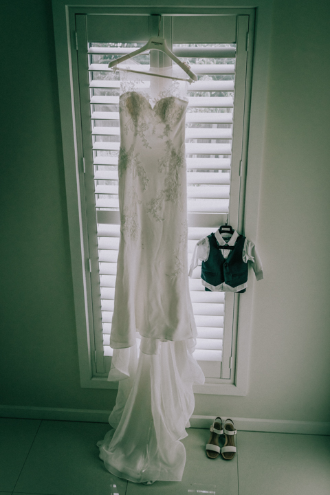 bridal wedding gown and baby wedding suit hanging at window in Homestead Mount Martha