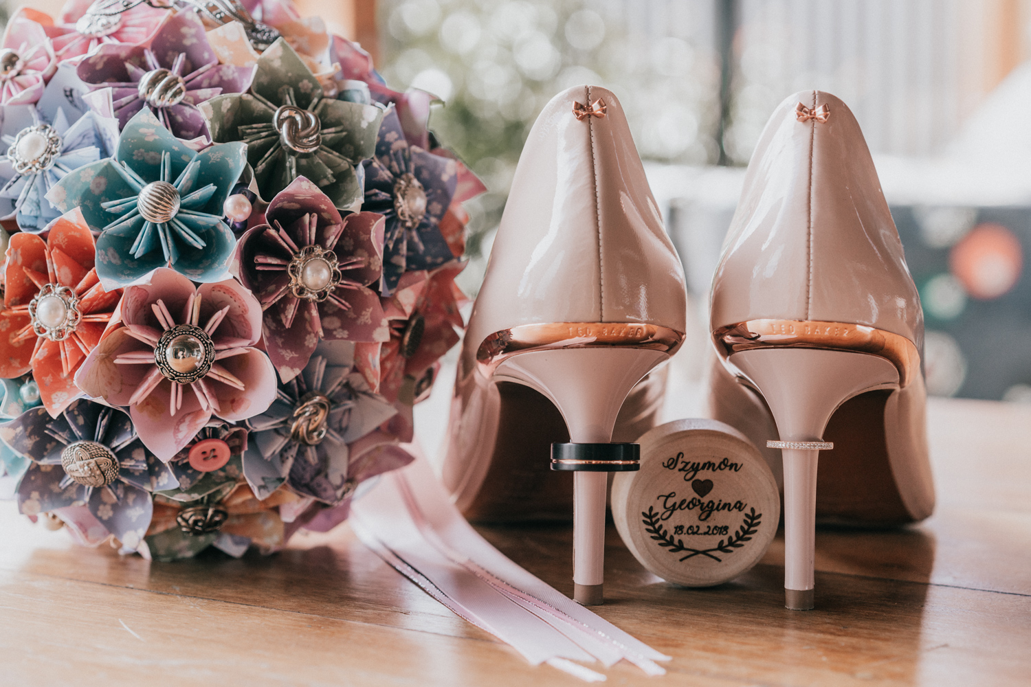 beautiful wedding photo of Ted Baker bridal shoes and bouquet and wedding rings in a barn wedding table