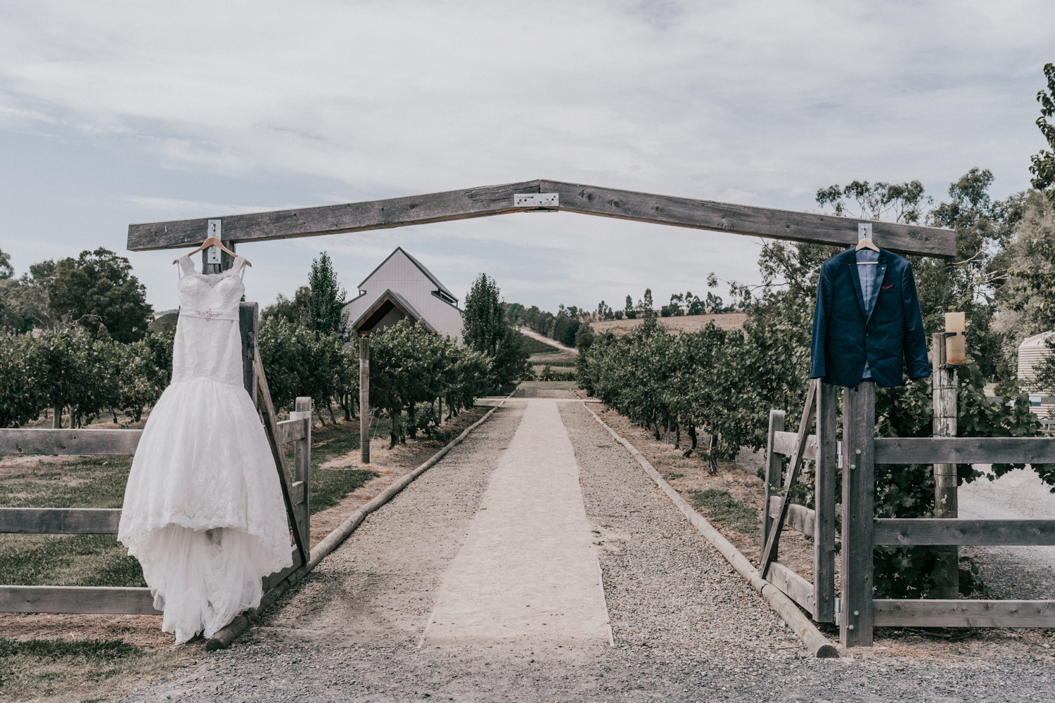 bridal dress and groom suit hanging outside rustic wedding Immerse Yarra Valley venue by Black Avenue Productions