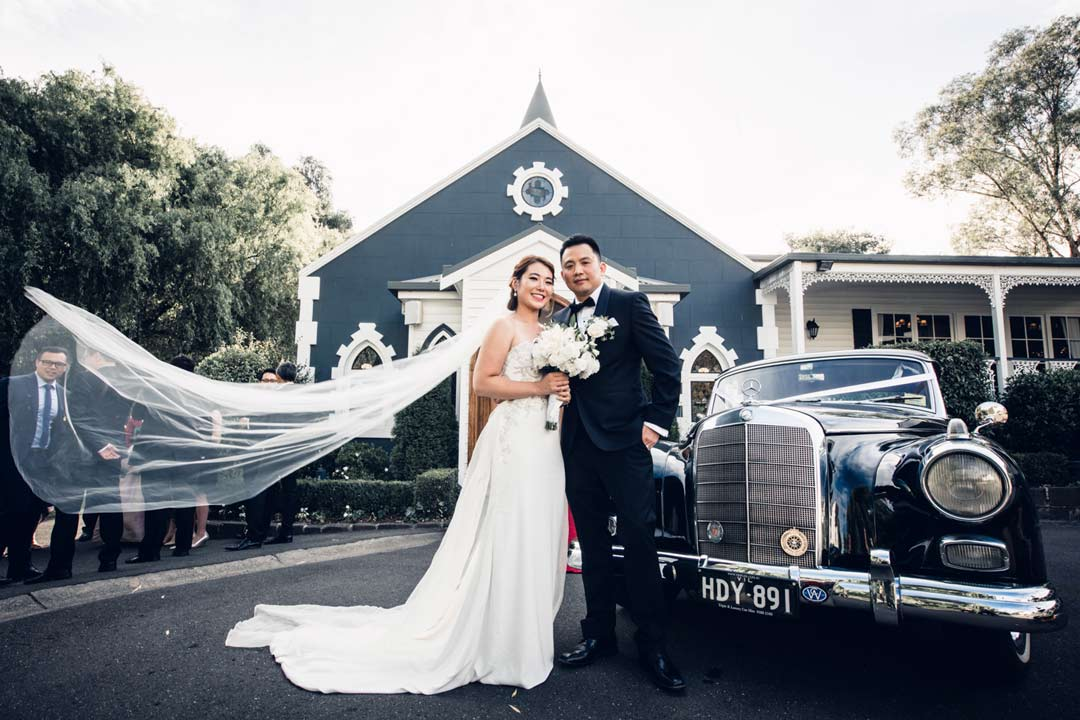 bride and groom standing in front of classic wedding car