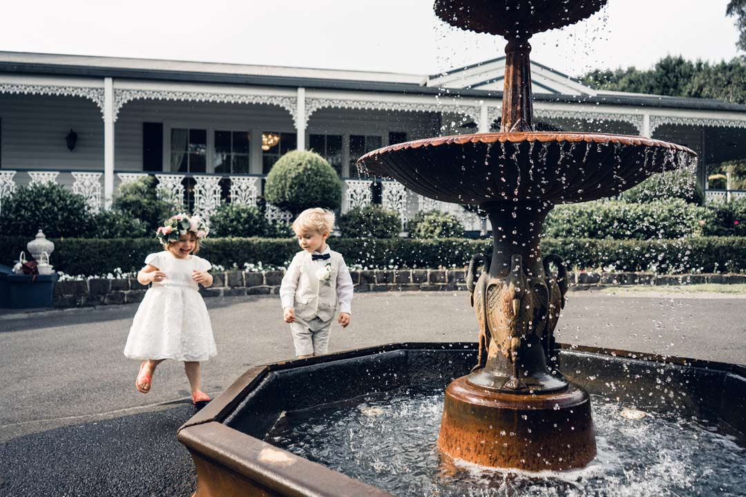 cute flower girl page boy playing with fountain at Ballara Receptions wedding venue