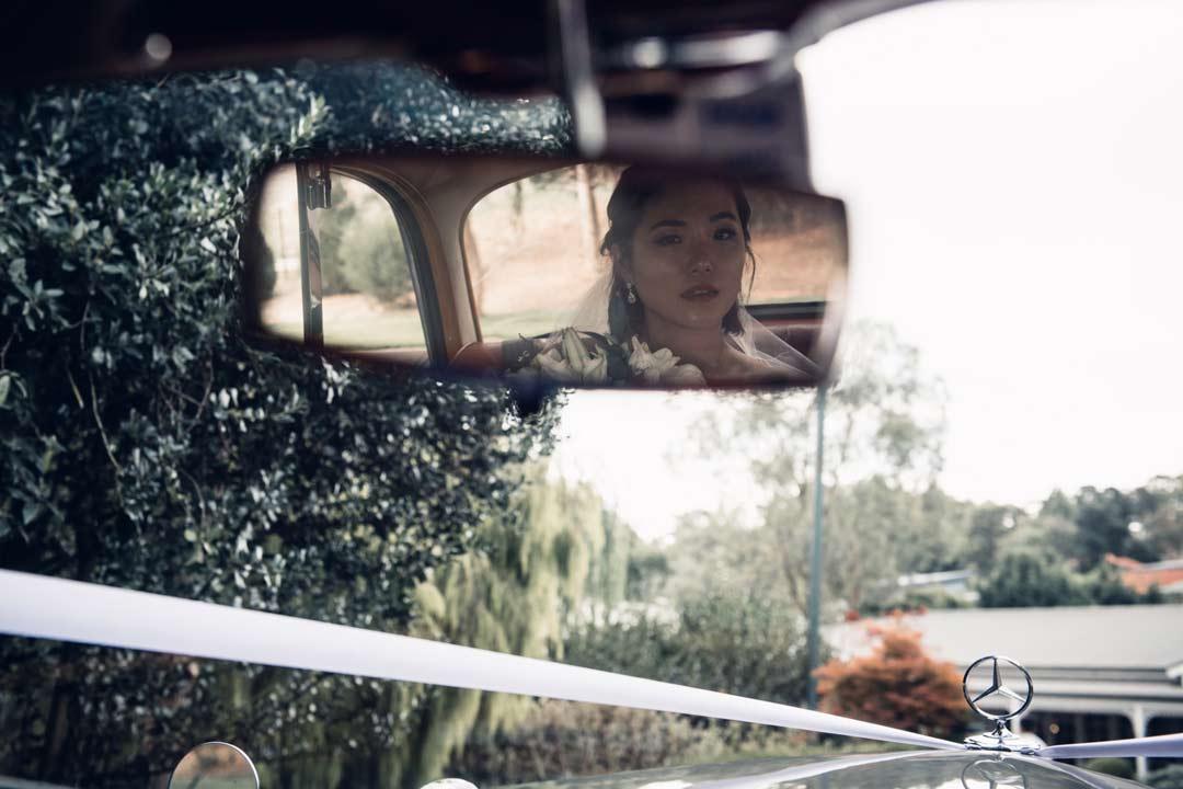 bride look at rear mirror in luxury classic rental wedding car by Triple R