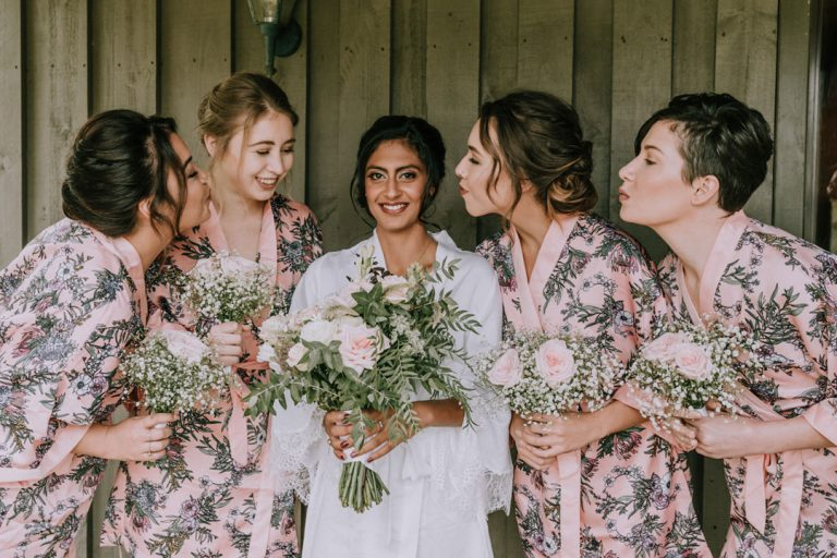 bride and bridesmaids kisses with bridal wedding flower bouquets