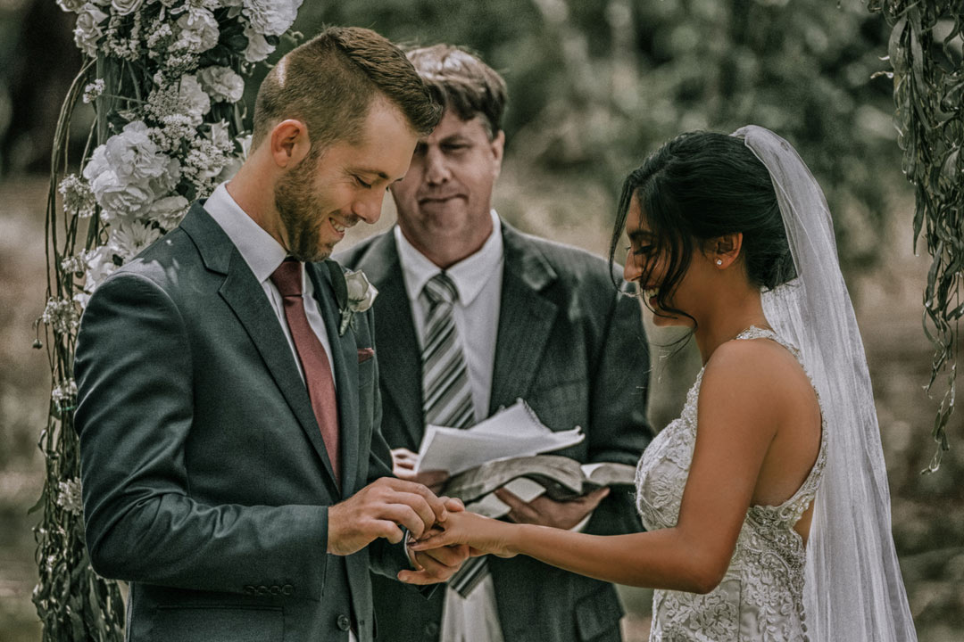 bride and groom exchange ring at rustic farm wedding Melbourne at altar