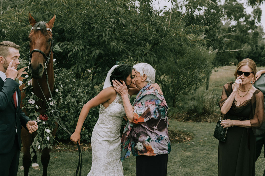 emotional moment of bride hug grandma while groom and mother crying after rustic wedding ceremony