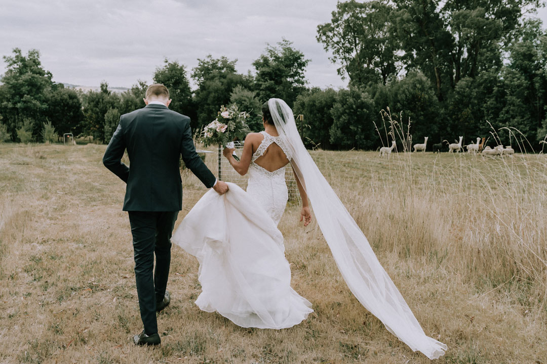 artistic candid wedding photo of bride and groom walking along the field