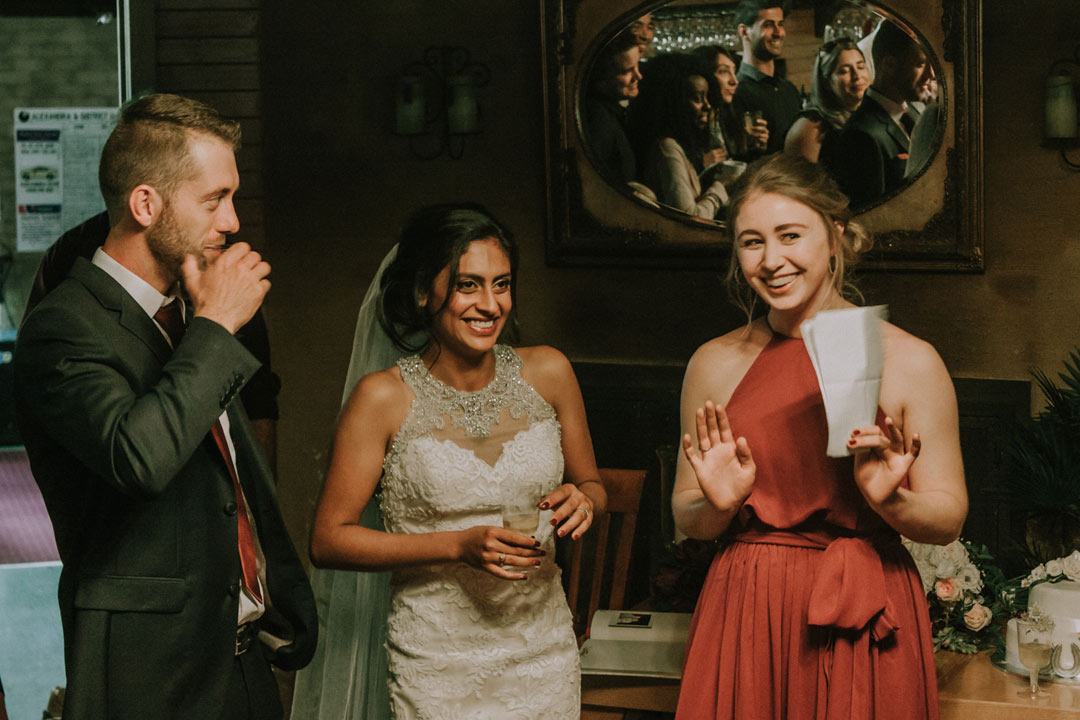 rustic wedding reception photo showing bridesmaid speech and bride laughing