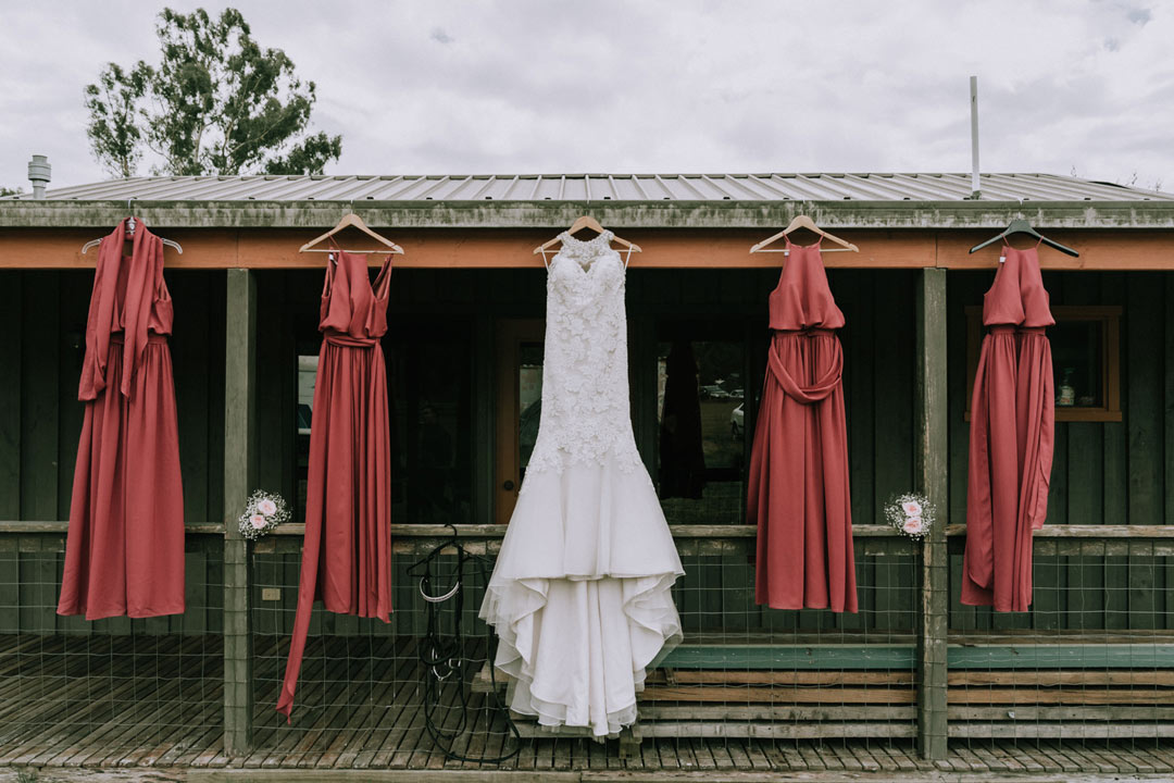 wedding dress and bridesmaid dresses hanging outside stone rustic farmhouse