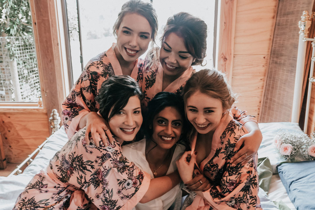 bridal party in bridesmaids robes hugging bride in a rustic stone house