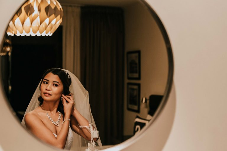 Beautiful Melbourne bride put on earring in front of mirror of Brighton Savoy Wedding reception hotel room