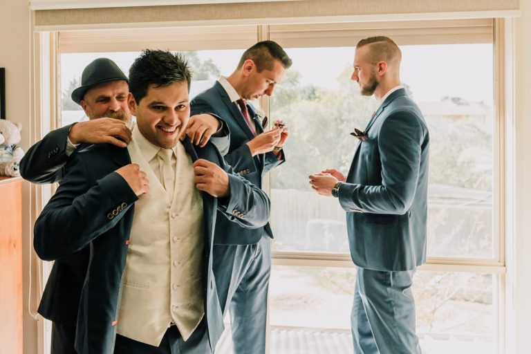 groom and groomsmen getting ready for wedding day in their Melbourne home candid shot by Black Avenue Productions