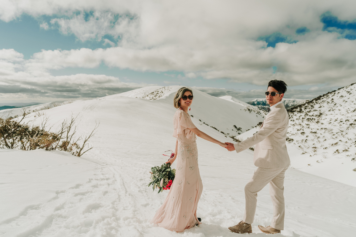 Melbourne couple in pink attire for snow engagement photos trip in snowy mountain Falls Creek by destination wedding photographers Lowina Blackman from Black Avenue Productions