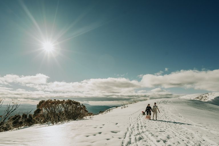 Photo of snow mountain at Hotham Victoria Australia with engaged couple Yolanda and Johnny walking uphill