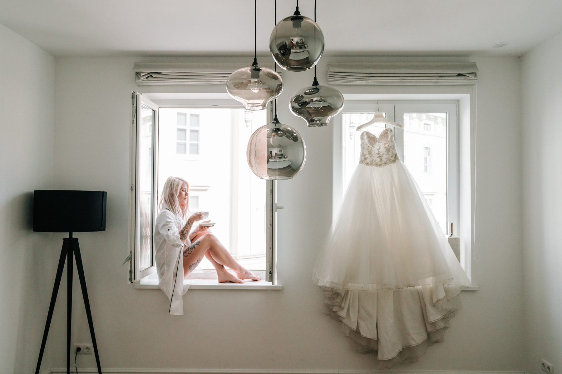 beautiful Vienna wedding photos of bride in boyfriend shirt sit by the window sip coffee before her wedding day