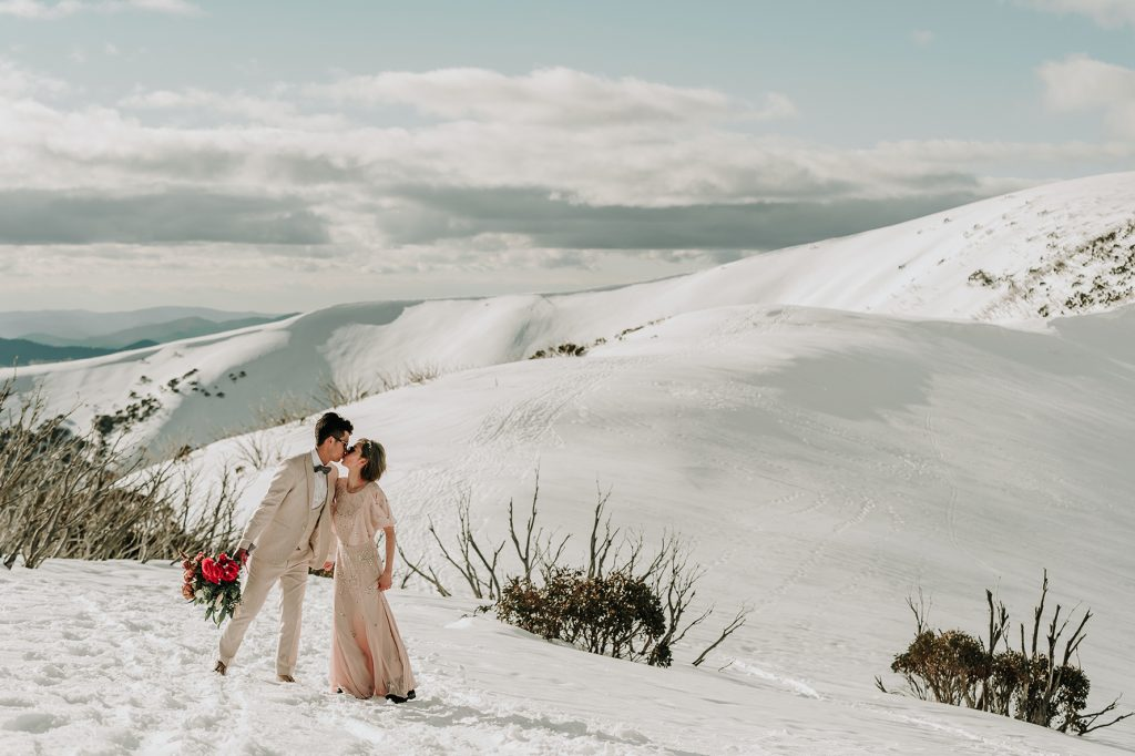 stunning Melbourne couple stood in front of Falls Creek mountain for their snow engagement photos shoot in honest wedding photography style