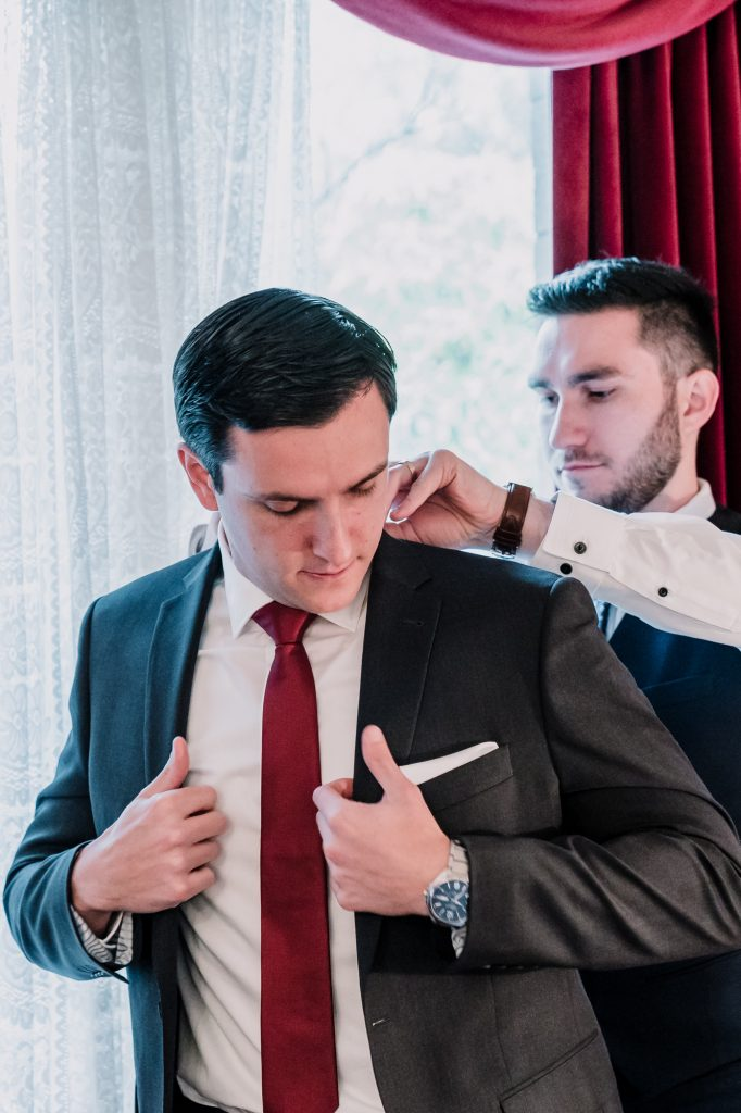 groomsman fixing jacket of groom, getting ready to marry