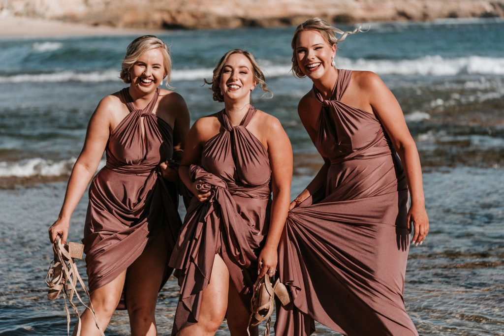 Bridal party photos by Sorrento All Smile beach wedding in Melbourne showing three lovely bridesmaids playing with the water in beige dresses