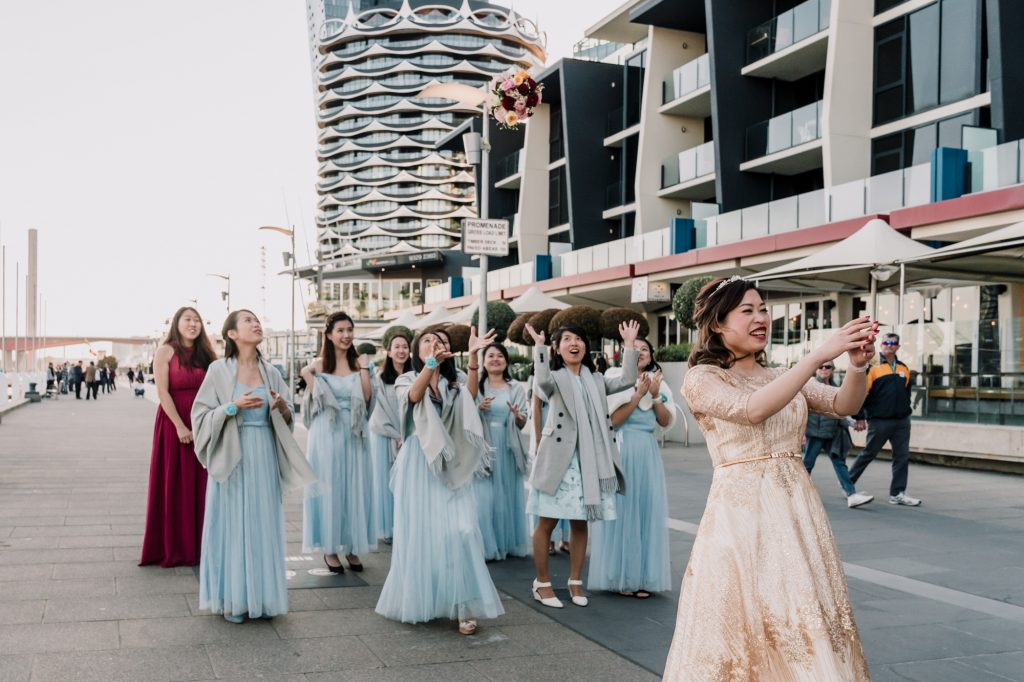 Melbourne bridal throw her bouquet at Docklands to her bridal party photos captured by Black Avenue Productions