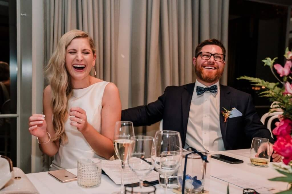 Bride and groom laughing so hard during speech on their Royal Melbourne Yacht Squadron wedding night photographed by award winning Australia wedding photographers Black Avenue Productions