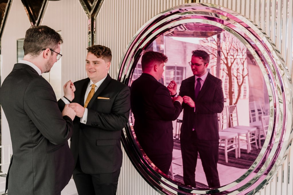 groom and groom getting ready for their Mon Bijou Melbourne Wedding photo in front of big round mirror