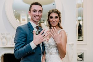 Melbourne couple showing off their wedding rings at their Brighton beach wedding reception as newly wed