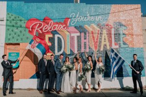 Bridal party strike a pose outside Edithvale wall on their brighton beach wedding day