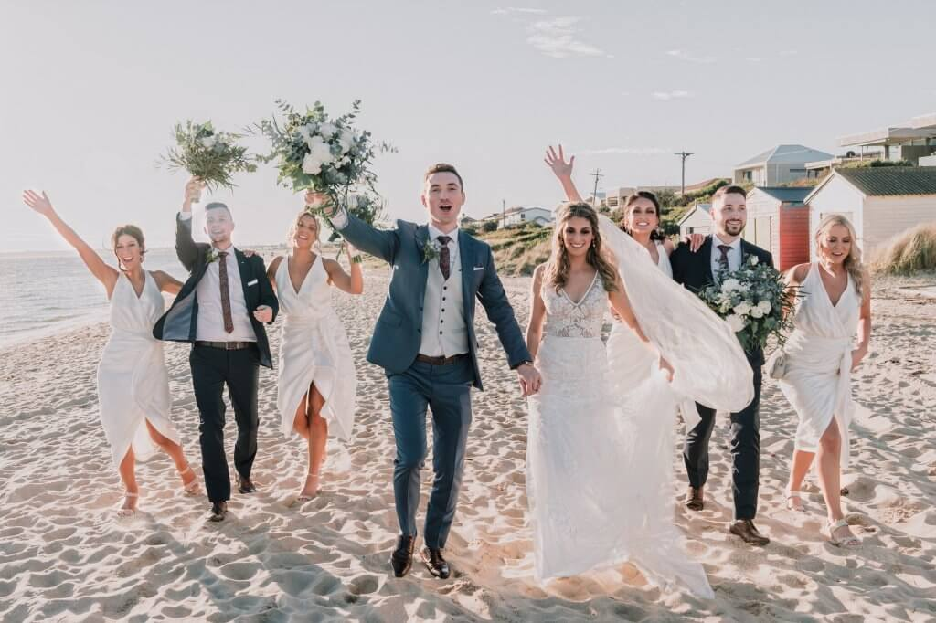 stunning group of bridal party marching on Brighton beach wedding venue captured by Black Avenue Productions
