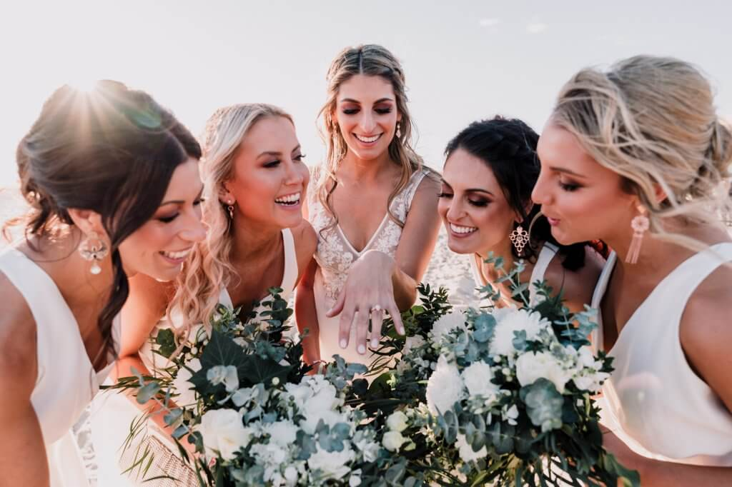 Bridesmaids admire diamond wedding ring of bride on her Brighton beach venue in backlit sunlight candid moment captured by award winning wedding photographer Derek Chan from Black Avenue Productions