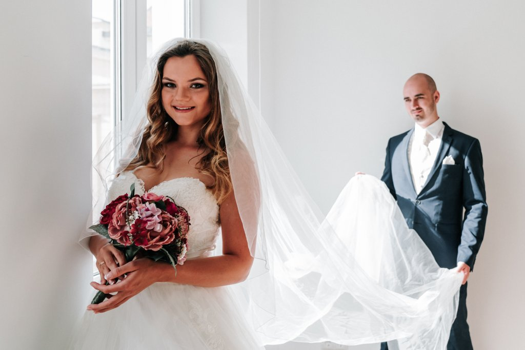 Blonde bride Marta with groom getting ready for Europe photo shoot in Vienna wearing wedding dress and bouquet captured by Black Avenue Productions