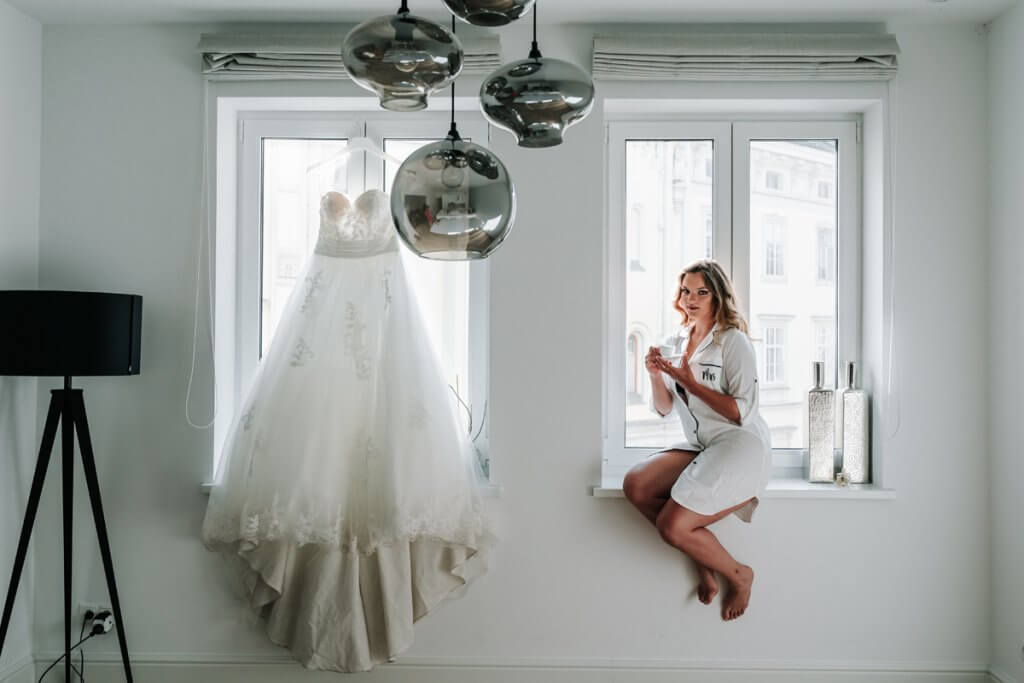Bride wearing silk gown sitting on window with wedding gown hanging for Europe photo shoot by Melbourne wedding photographers Black Avenue Productions Derek Chan and Lowina Blackman