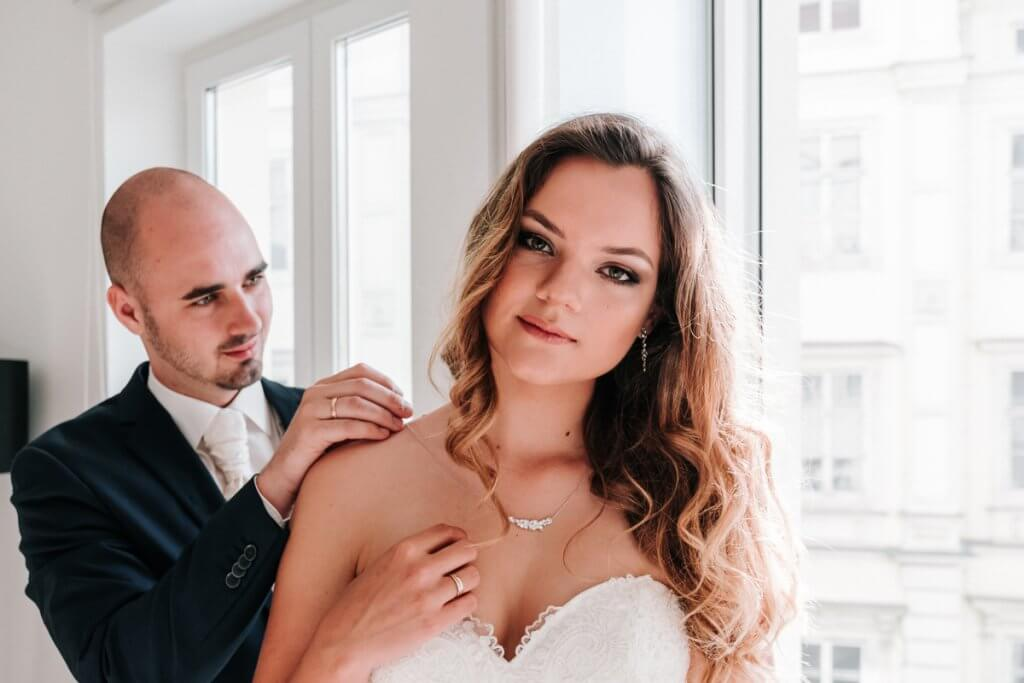 beautiful blonde hair bride Marta look at camera for Europe photo shoot with husband Stefan help her wearing wedding necklace in Vienna apartment