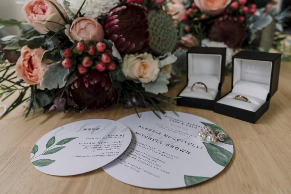 lay flat wedding photo of Alessia and Mitchell wedding invitation set with wedding rings flowers by Black Avenue Productions