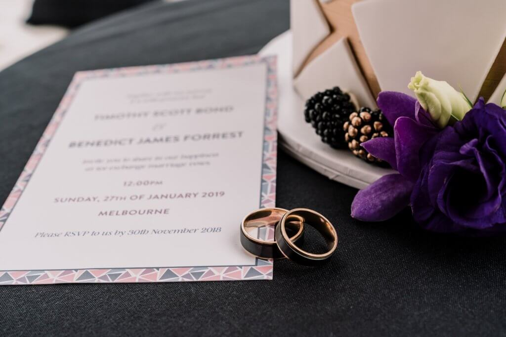 Melbourne gay couple Tim and Ben wedding invitation card with black stylish wedding rings for men and gay wedding cake featuring purple and gold flakes and flowers