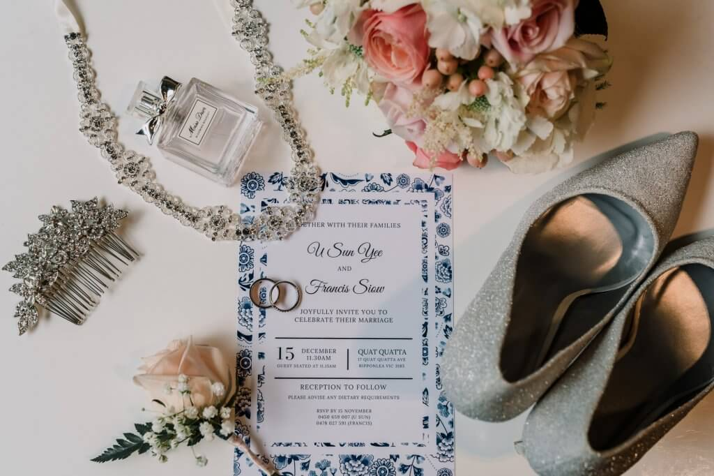 wedding invitation card and RSVP card set sample with wedding items shoes necklace flowers on a lay flat wedding photography style by Black Avenue Productions