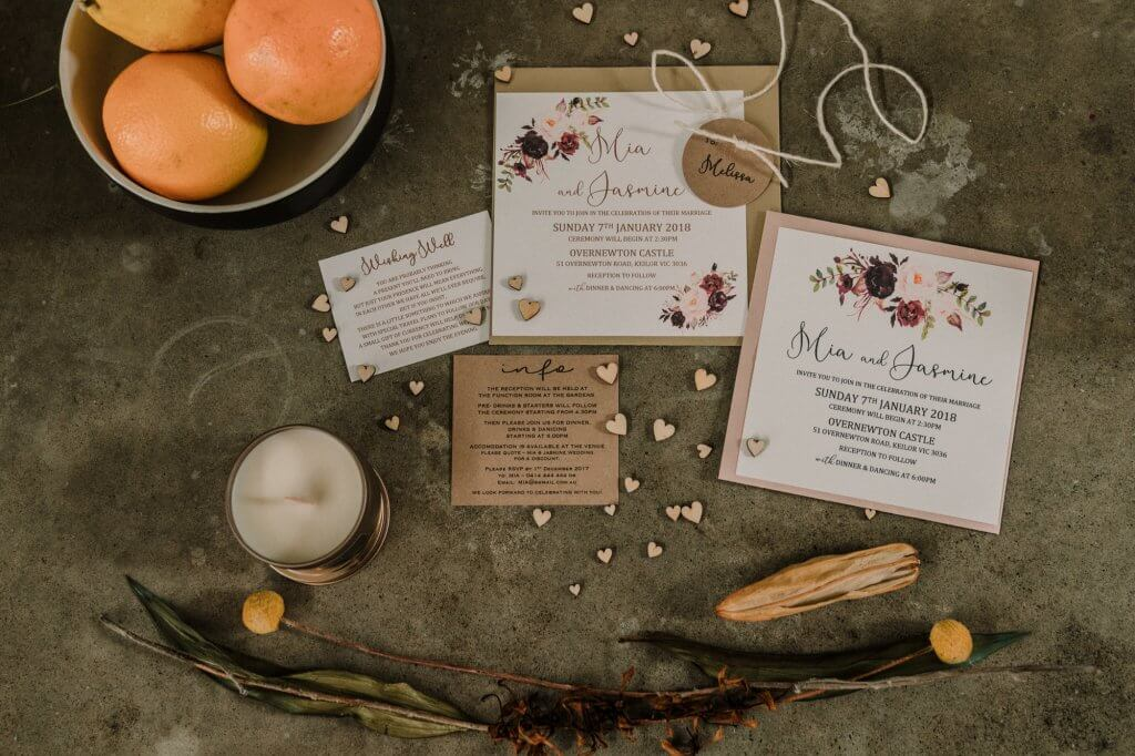 wedding invitation photo of same sex couple wedding invitation set including RSVP save the day in lay flat photography style with oranges candles and love heart decorations captured by Black Avenue Productions