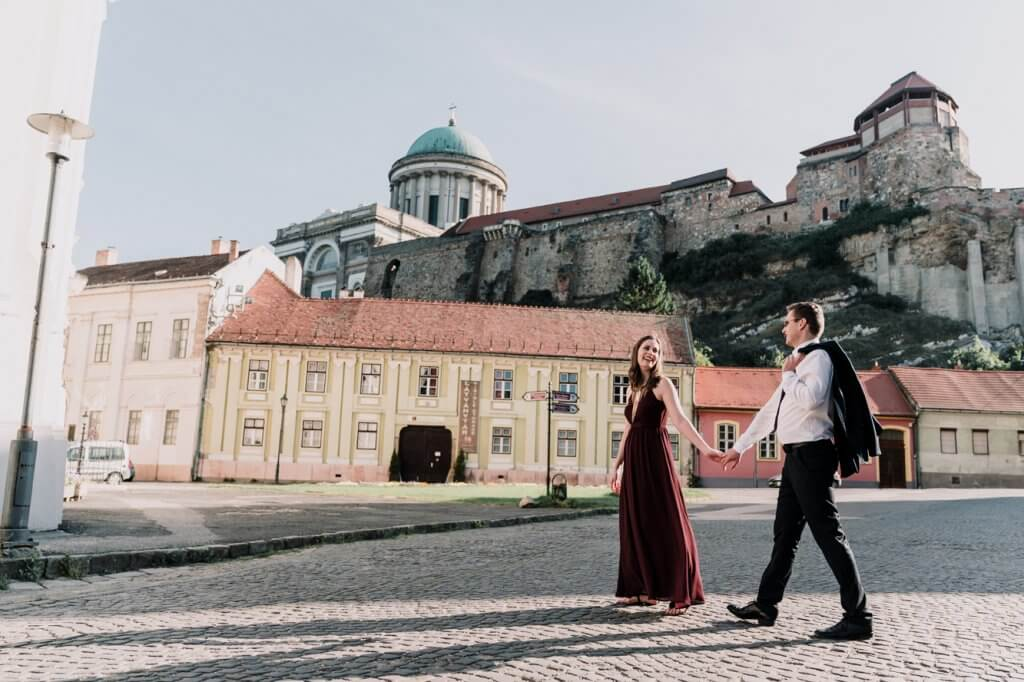 Melbourne couple walking across European castle for their engagement photoshoot by destination wedding photographer Derek Chan from Black Avenue Productions