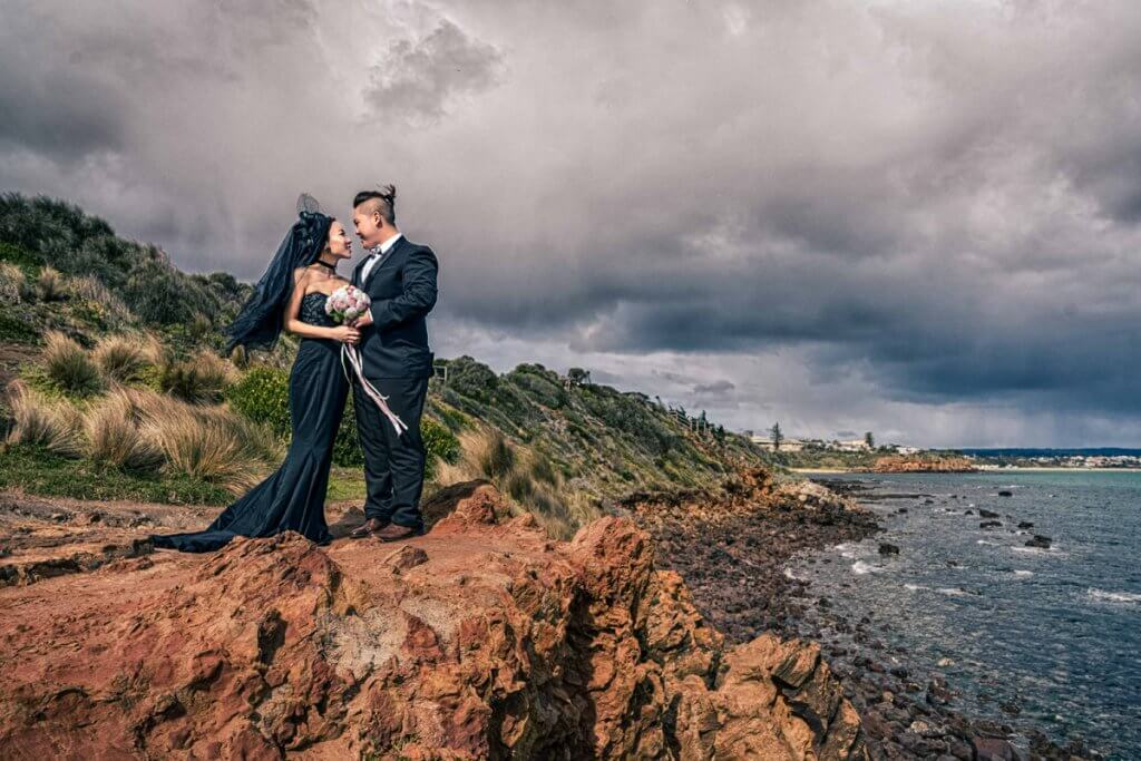 Mornington Peninsula engagement photoshoot image featuring Melbourne couple in black silk gown on a cliff overlooking the ocean in an artistic moody edgy colour tone and candid photography style