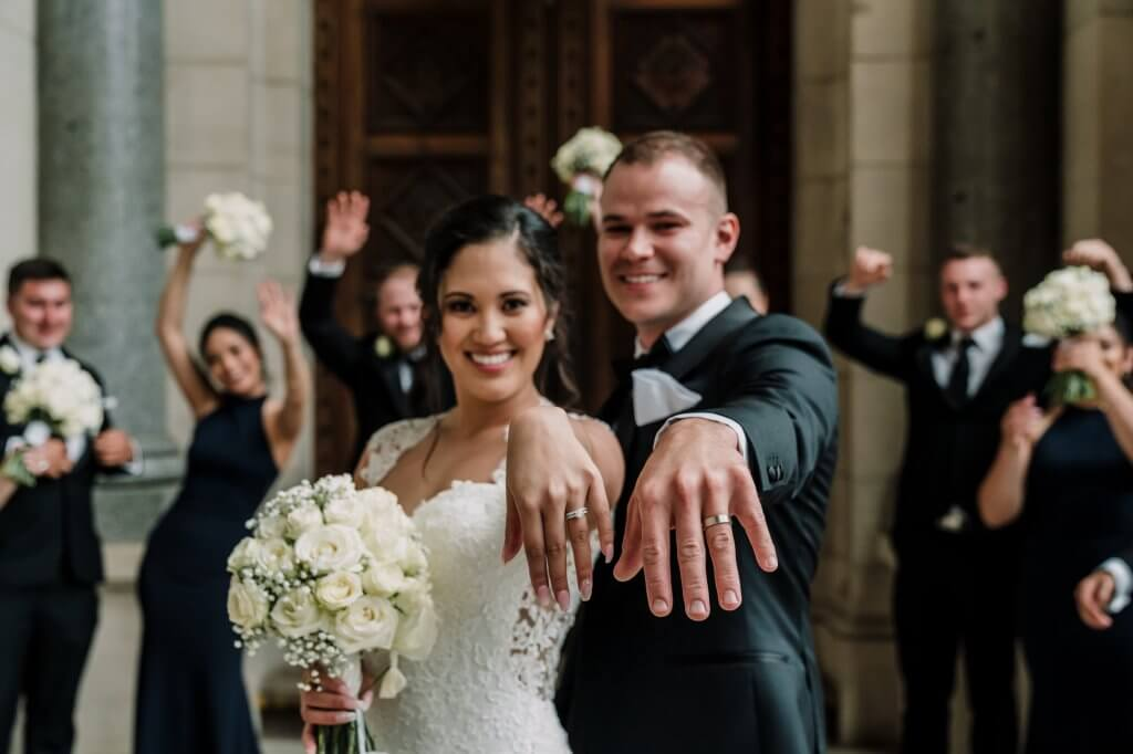 Happy Melbourne couple show off wedding rings to bridal party at Manor on High wedding venue taken by Black Avenue Productions