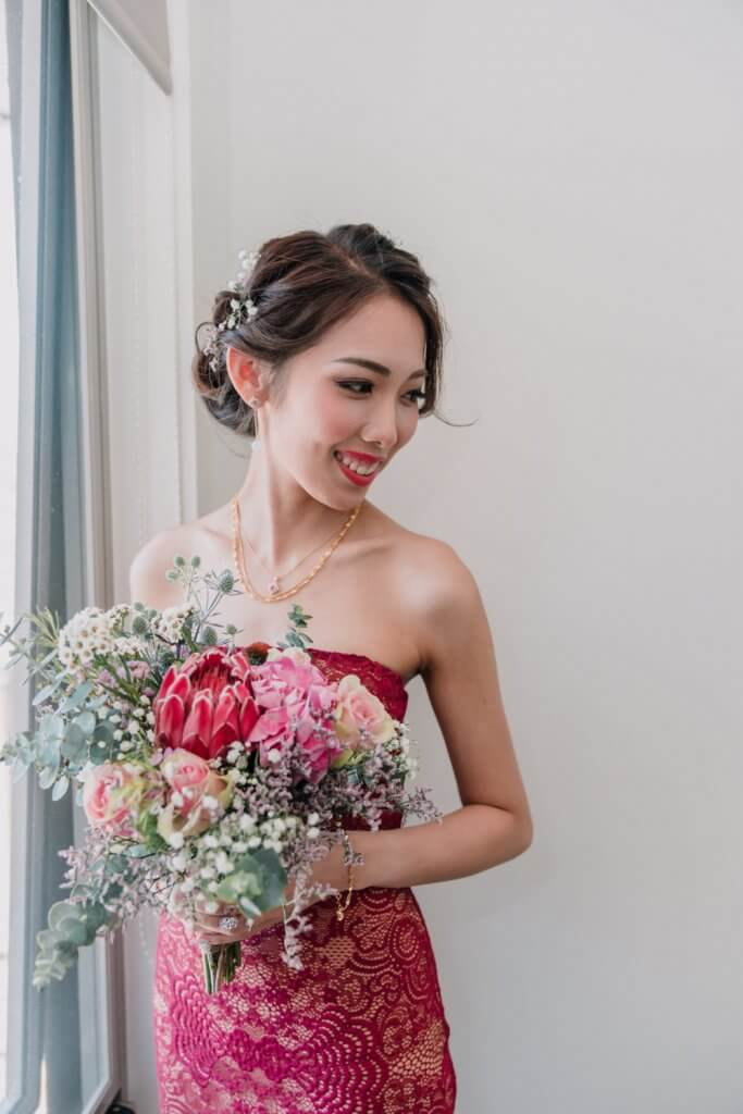 Asian bride wearing a red dress holding a bouquet of flowers