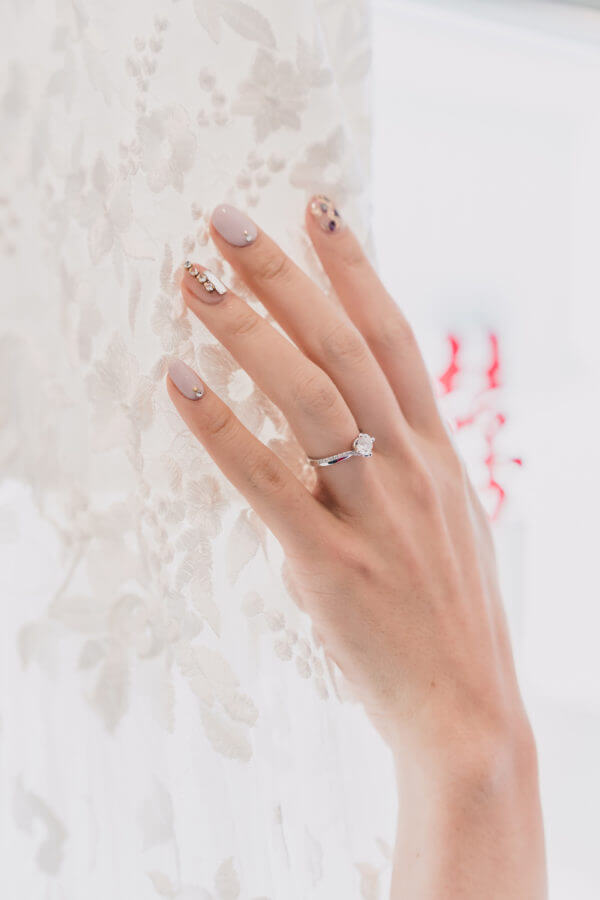 Hand wearing a ring with pink designed nails
