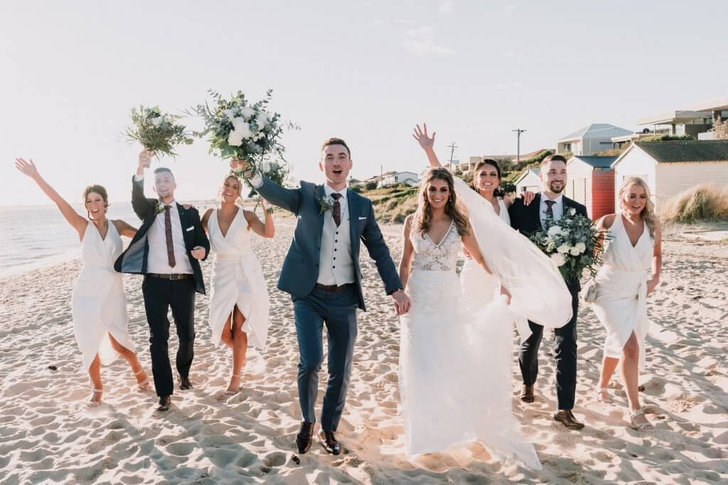 Bride and groom together with their bridesmaids and groomsmen having fun in the beach during the golden hour photographed by