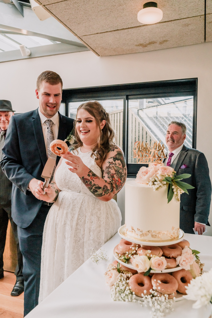 bride and groom cutting a doughnut before cutting their wedidng cake
