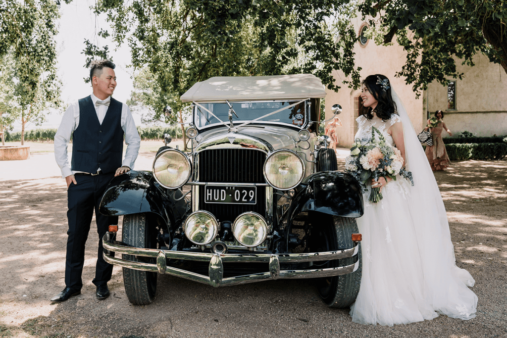 bride and groom with black vintage car in wedding day