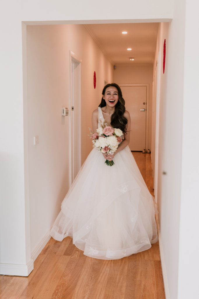 asian bride in white gown with flower bouquet