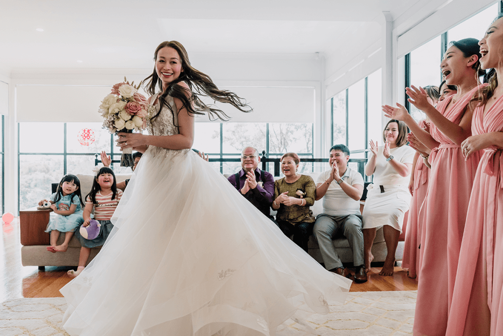asian bride showing her wedding gown to her family