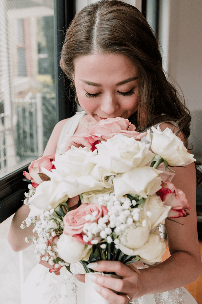 bride wearing white gown holding bouquet with pink and white roses
